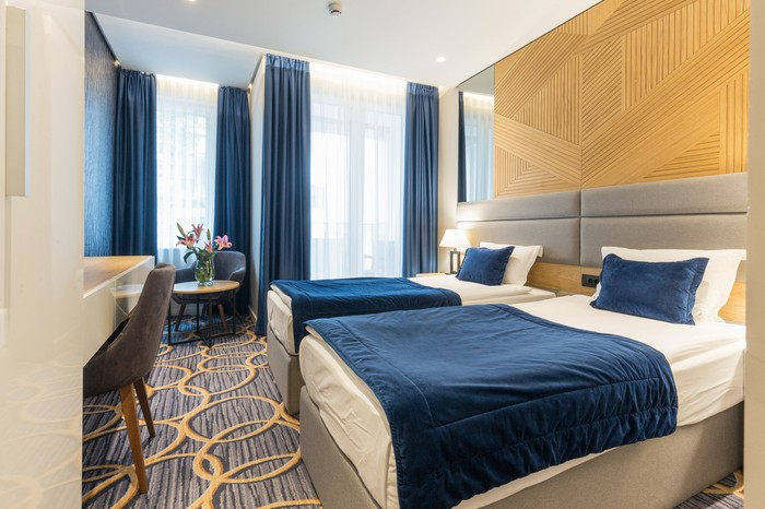 Hotel room with two single beds and blue curtains