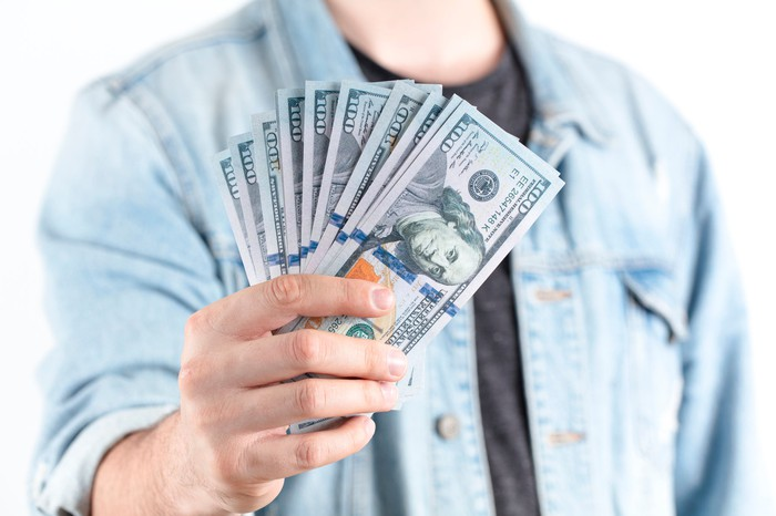 A man wearing a denim shirt holds out a handful of $100 bills.