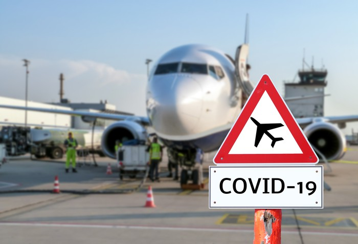 Photo of COVID-19 sign beside a commercial aircraft.