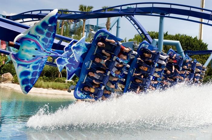 Riders on SeaWorld Orlando's flying Manta coaster skim along the water.