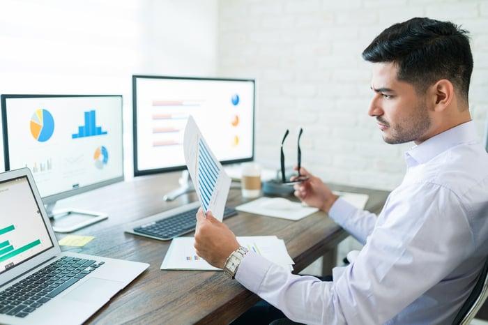 A man looking at several different monitors displaying data.