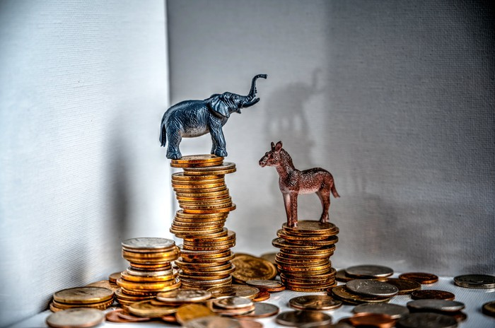 An elephant figurine on a coin stack towering over a donkey figurine on a coin stack.