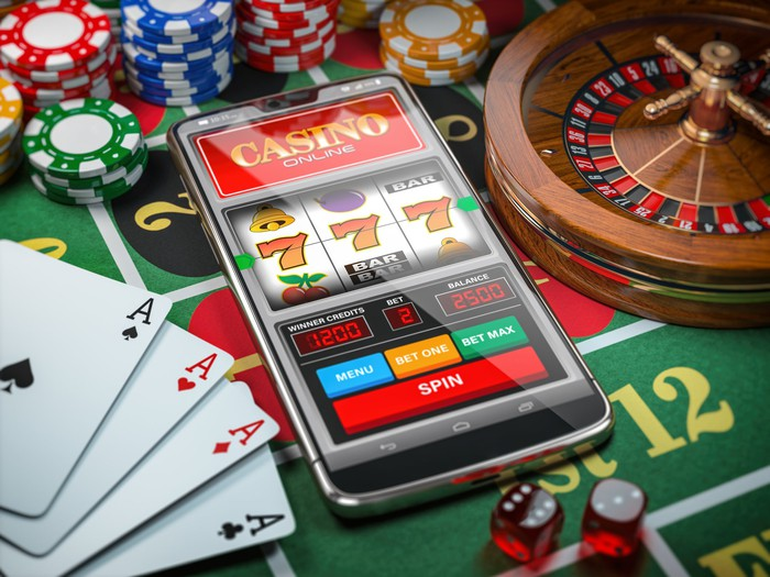 A smartphone with a casino website lying amid dice, cards, poker chips, and a mini roulette wheel.