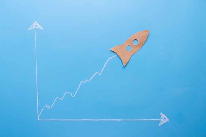 A paper cutout of a rocket at the tip of an ascending chart line.