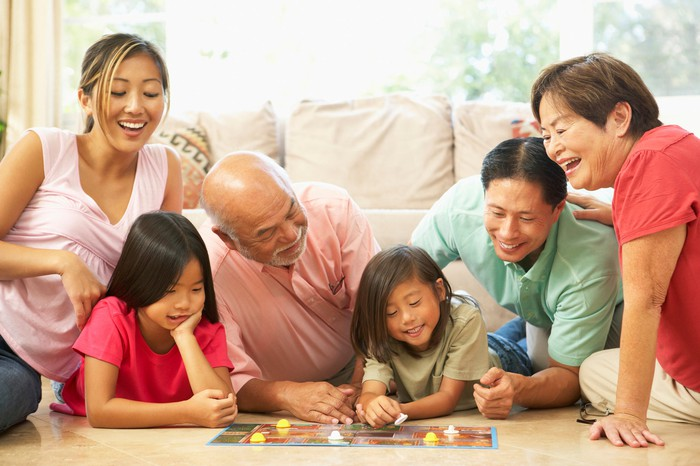An extended family from children to grandparents playing a board game.