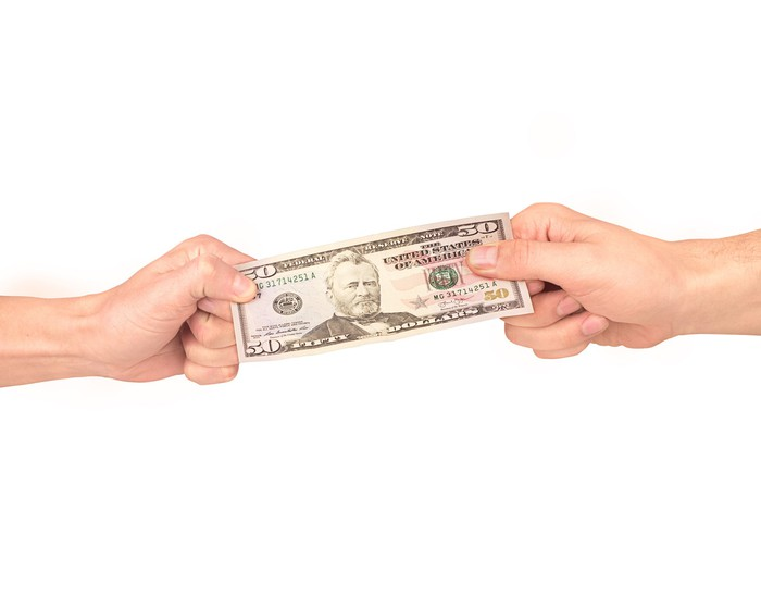 Two hands pulling a fifty-dollar bill in a tug of war.