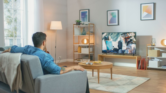 A man watching television in a living room.