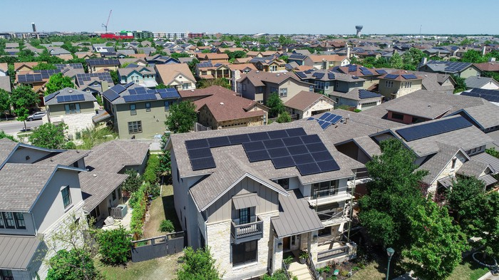 Aerial view of neighborhood with solar panels on many roofs.
