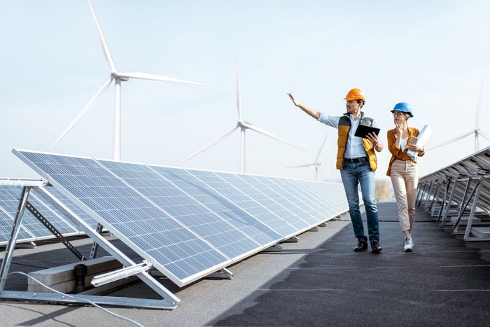 Two workers walk past a solar plant with wind turbines in the background