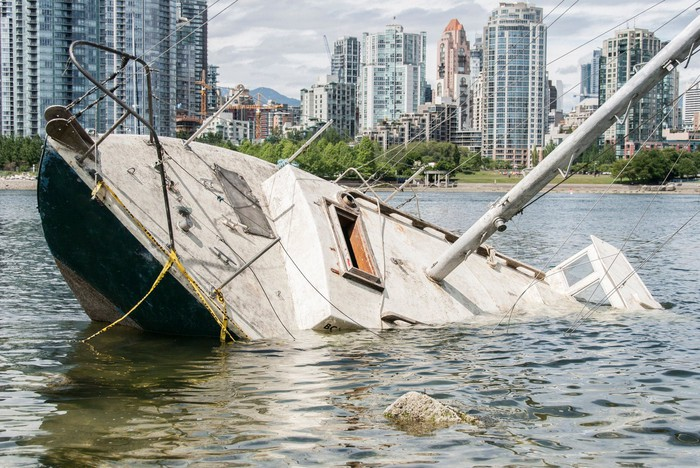 Boat sinking in front of a waterfront city