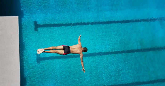 Person in mid-dive into a swimming pool.