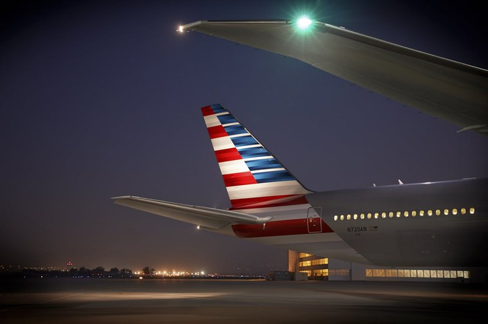 An American Airlines airplane tail lit up at night.
