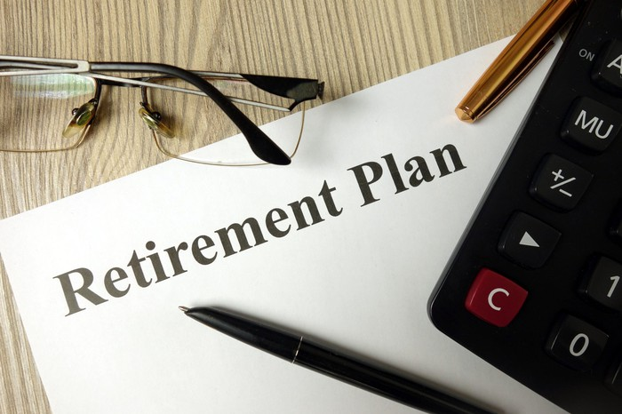 Retirement plan folder on a desk with pens, a calculator, and glasses.