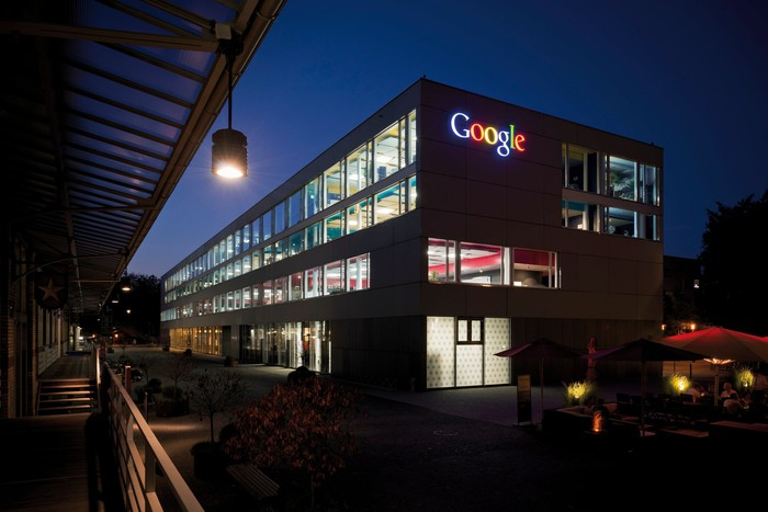 A building lit up at night with the Google logo near the roof.
