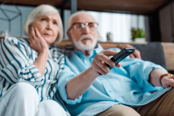 An older couple seem worried as they watch TV on their couch.