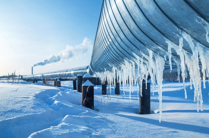 An oil pipeline covered with icicles in a snowy landscape.