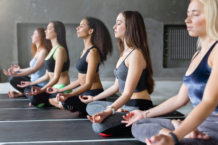 A group of women attend a yoga class.