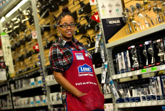 Lowe's plumbing department employee stands in an aisle.
