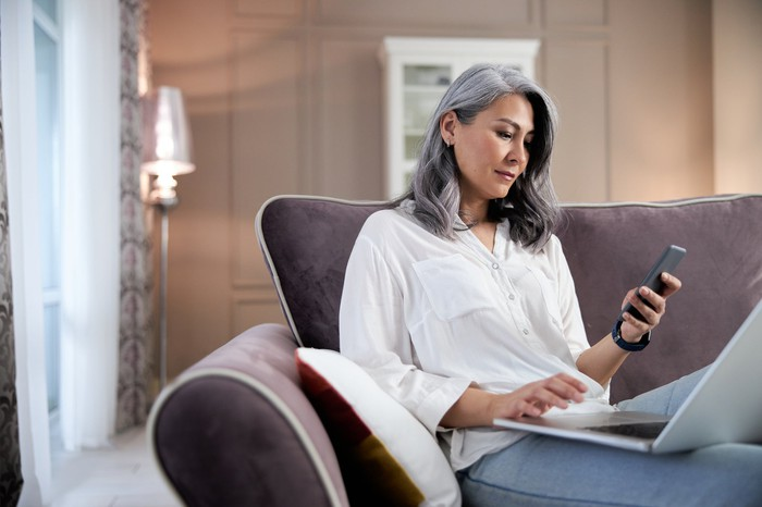 Old woman looking at phone with laptop on couch at home.