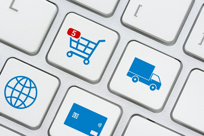 A computer keyboard with icons of a shopping cart, a delivery truck, a globe, and a credit card on four of the keys.