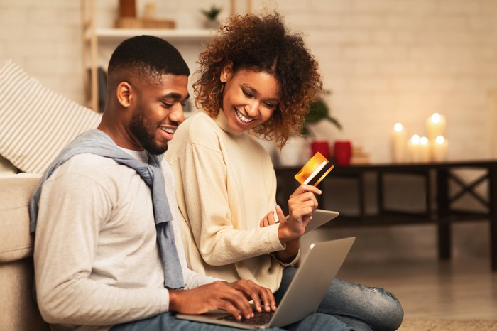 A couple with a laptop and a credit card shopping online.