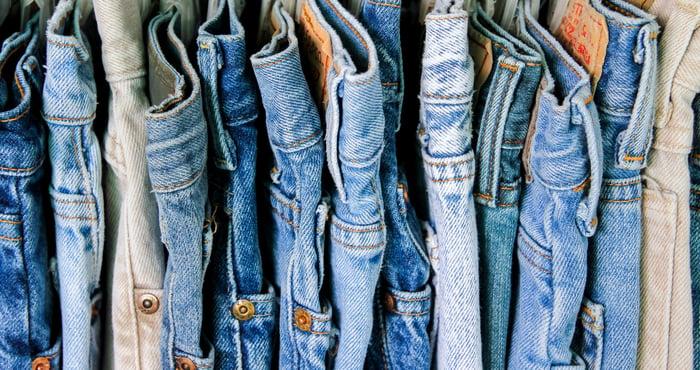 Line of denim jeans hanging on a rack.