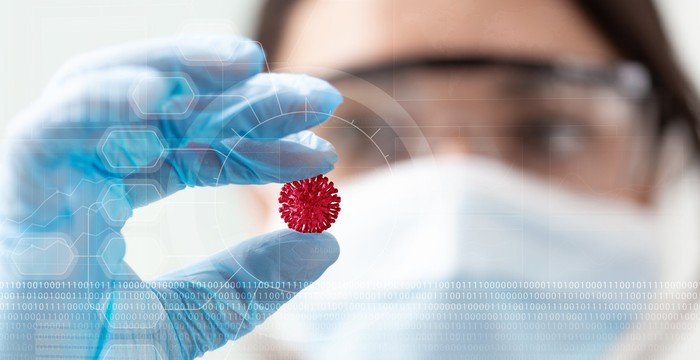 Scientist holding a small coronavirus model.