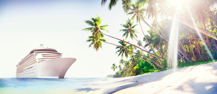 Cruise ship next to a sunny beach with palm trees