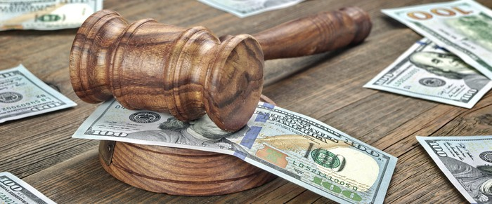 A judge's gavel on a desk covered by one hundred dollar bills.