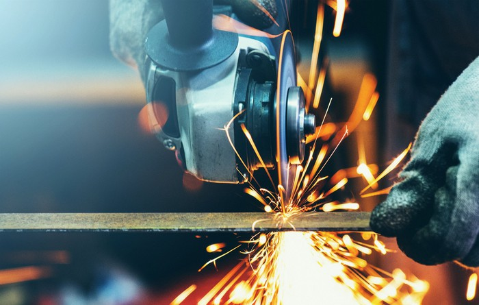A worker grinds a steel tube in a machine shop.