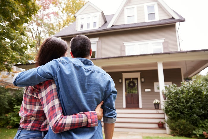 A couple embraces while looking at their new home.