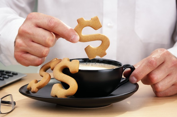 An investor dunks dollar sign-shaped cookies into his coffee.