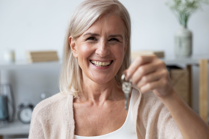Older woman smiling holds out house key.