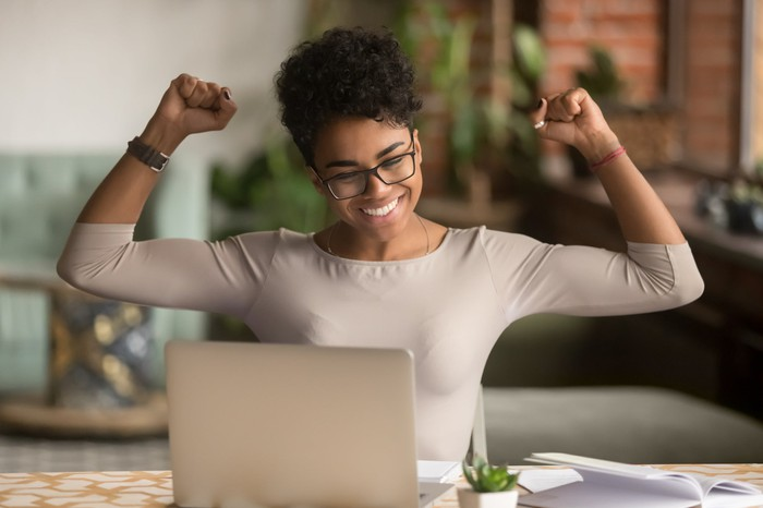 A woman raising her arms in triumph in front of a computer