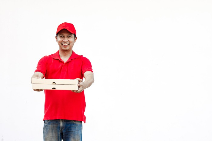 A man in a red shirt and hat is holding two pizza boxes.