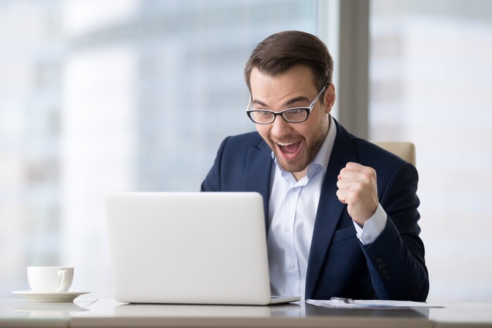 Man in business suit at laptop holding fist up in celebration