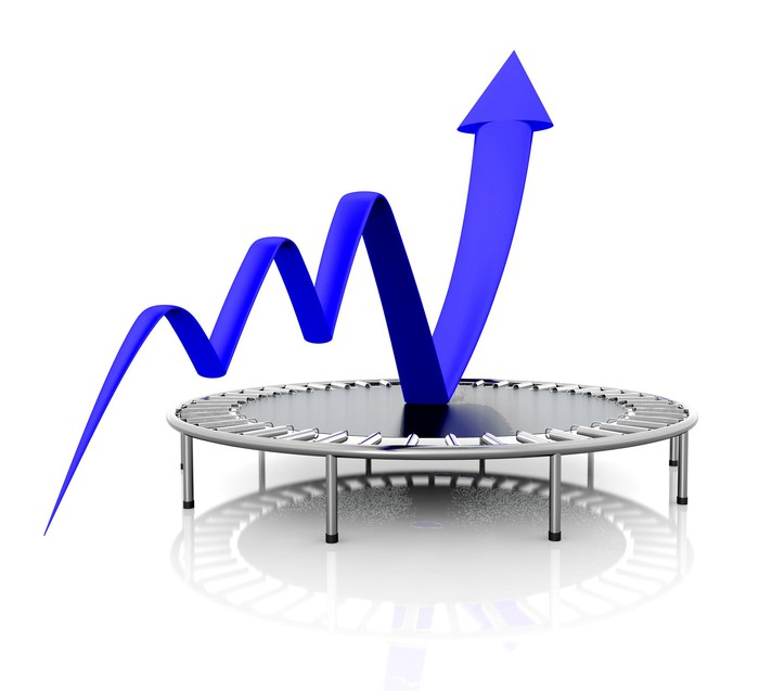 A blue charting arrow bounces upward on a black trampoline.