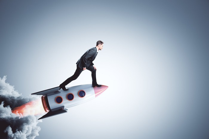 A businessman stands on the nose of a rocket speeding upward.