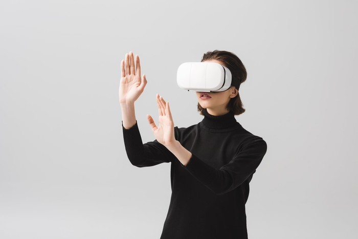Young woman raising hands while wearing a virtual reality headset.