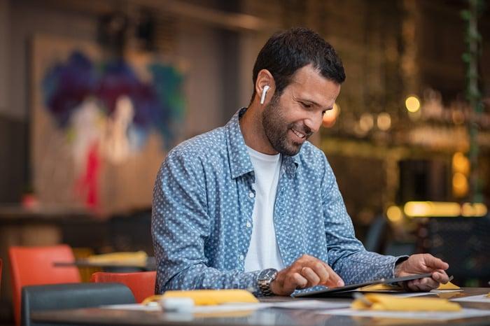 A man wearing wireless in-ear headphones.