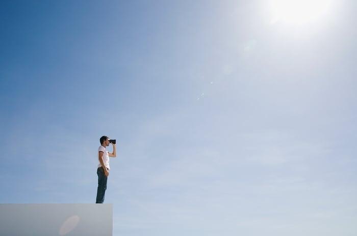 Man in the distance looking through binoculars under a blue sky