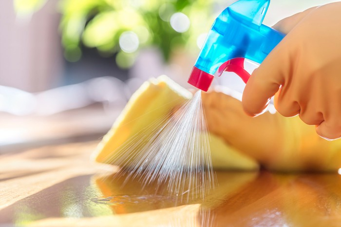 A person cleaning a surface with a spray bottle and cloth.