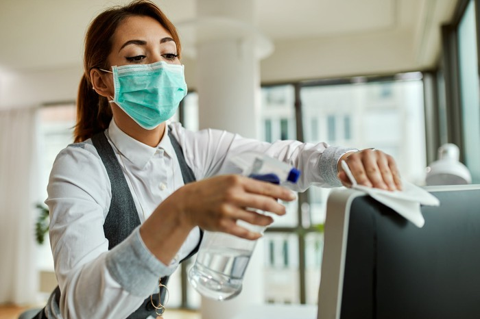 A woman wearing a mask cleans a television set.