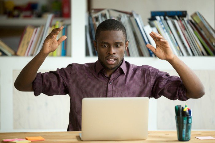 A young man is staring at his laptop in surprise, his arms held up.