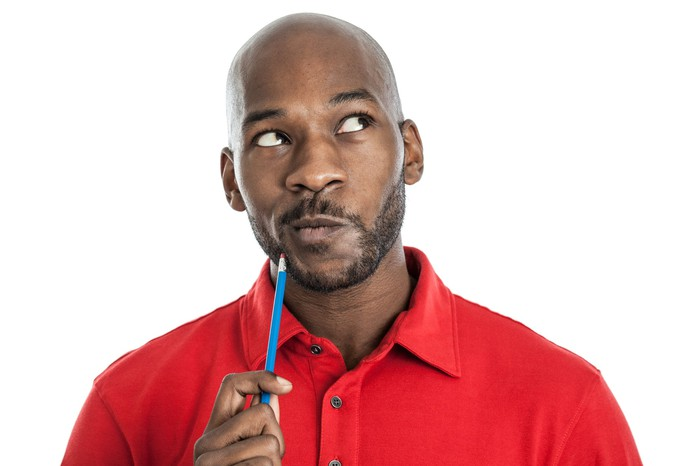 A young man holds a pencil to his chin while thinking.