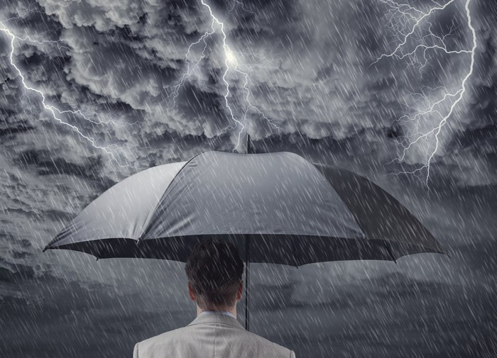 Man holding an umbrella in a thunderstorm