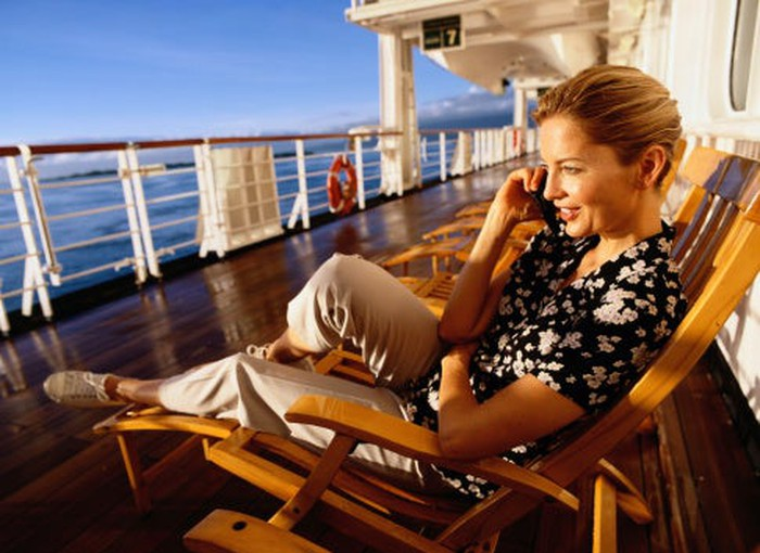 A lady relaxing on an outdoor cruise deck while on the phone.