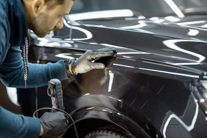 A man inspecting a vehicle.