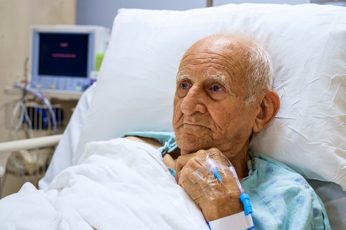 Older person in hospital bed.