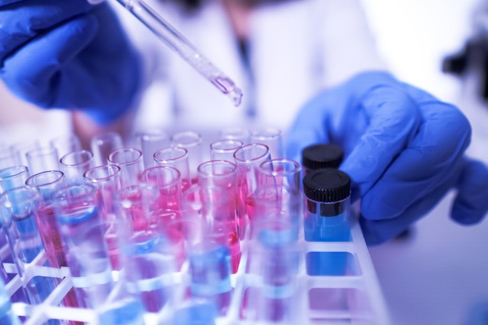 Scientist holding dropper over test tubes